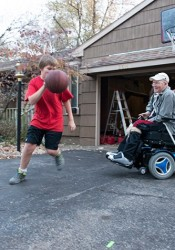 Prairie Village resident Finn Bullers and his son, Christian, 13, play a spirited game of one-on-basketball while waiting for a nurse to perform Dad's daily respiratory treatment. Photo courtesy of Sabrina Staires, sabrinastaires.com.