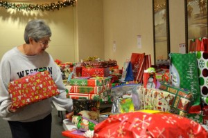 Volunteer Theresa Blizman sorts presents on tables for individual families at the Sylvester Powell Community Center.