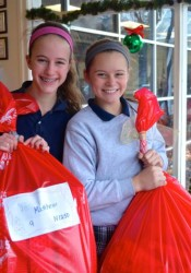 St. Ann students Jacqueline (L) and Ellie Platt load bags of gifts at the school Friday afternoon.