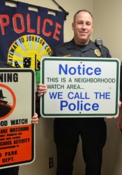 Roeland Park corporals Warren Gardner (L), and Charlie Kotcher and Police Chief John Morris (R) display some of the old neighborhood watch signs from years ago.