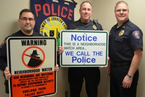 Roeland Park corporals Warren Gardner (L), and Charlie Kotcher and Police Chief John Morris (R) display neighborhood watch signs.