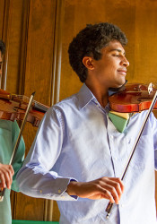 Akshay Dinakar (right), seen practicing violin with his brother Bhavish, is among this year's National Merit Semifinalists from SM East.