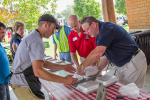 Competitors at last year's Battle of the Brisket bring their offering to  the judges table.