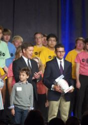 Shawnee Mission Superintendent Dr. Jim Hinson was joined on stage by choir members at the five high schools and students who took part in the program at the conclusion of the SMEF breakfast this morning at the Overland Park Convention Center.