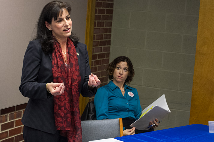 Incumbent Melissa Rooker, standing, and challenger Jennifer Robinson spoke before a crowd of approximately 40 at the Cedar Roe Library Thursday.