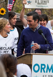 Greg Orman and his wife, Sybil, were flanked by supporters waving signs as he made his remarks in Prairie Village Sunday.