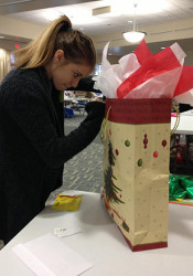 Mia Rothrock, daughter of Mission City Councilor Arcie Rothrock, helped wrap a gift Sunday.