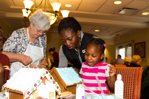 Teni Oyetunji, 3, was all smiles as she decorated her gingerbread house with the help of her mother Kiki.