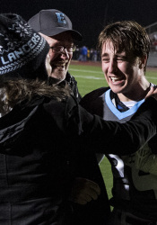 Sam Huffman hugged his parents, Doug Huffman and Mary Sinclair, after his gutsy two-point conversion run pushed the Lancers past Olathe North in the substate game.