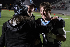 Sam Huffman hugged his parents, Doug Huffman and Mary Sinclair, after his gutsy two-point conversion run pushed the Lancers past Olathe North in the substate game in 2014.