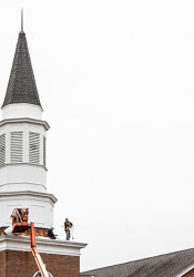 Crews worked to detach the steeple structure Tuesday.