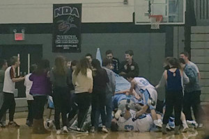 SM East players piled on the court after Joseph Brouillette's half court shot gave them a last-second win over rival SM South. Photo via SME Cheer Twitter.