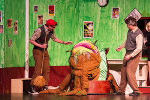 Seymour, played by Austin Dalgleish, and Mushnik, played by Tyler Armer, admire a fully grown Audrey II, the blood thirsty plant in SM East's production of Little Shop of Horrors.