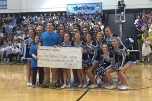 SM East cheerleaders presented a check to Farmer's House at half time of Friday's basketball game.