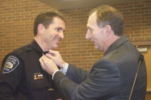 Tim Schwartzkopf, the newly-named  police chief for Prairie Village, get his new insignia pinned on by former chief Wes Jordan.