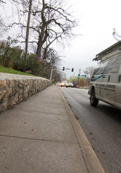 Traffic zips by the adjacent sidewalk on Mission Road where a retaining wall would make it hard for pedestrians to avoid a vehicle out of control.