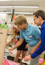 """Prairie students Maisie, Evan and Aaron made the glass shelves of a display case shine as part of their participation in """"Village People"""" Thursday."""