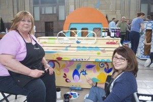 Christine Webster and Lanee Morales decorate the Roeland Park piano over the weekend at Union Station.