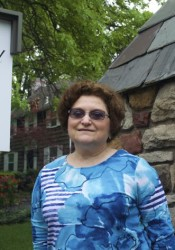Westwood Hills Mayor Paula Schwach at one of the stone entry markers to the city.