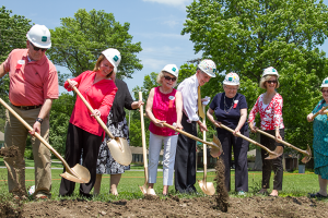 Village Presbyterian Church's founding pastor Bob Meneilly, in white shirt, was among the group to turn over the first shovel of dirt at the groundbreaking ceremony for the newVillage Church Child & Family Development Center.