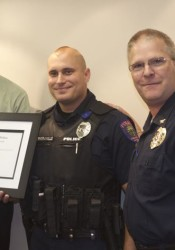 Roeland Park Mayor Joel Marquardt, Officer Mark Engravalle and Police Chief John Morris as Engravalle was give the Meritorius Conduct Award Monday.