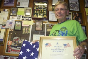 Johnny Pieters at Merriam Feed with the flag given to him by Stoney Bogan. His Vietnam medals are in a case behind him.