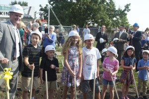Trailwood Elementary Principal Greg Lawrence is joined by students to turn the first dirt at the groundbreaking for the new school.