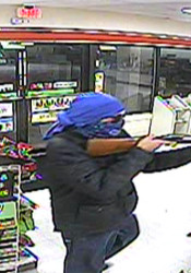 Footage from the 7-Eleven surveillance camera shows the robber pointing a gun at the clerk.