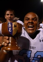 Senior Calen Gilmore carries the Nut Cup to the locker room after a 42-21 victory. Photo by Joseph Cline