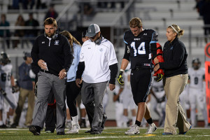 Senior Luke Heisdorffer is walked off the field by Coach Delaney after a possible season ending injury to his arm. Heisdorffer was later taken to the hospital for further examination of the injury. Photo by Joseph Cline