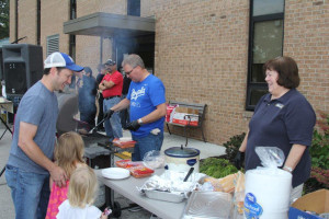 Police Chief John Morris mans the grill at Roeland Park's Night Out event.