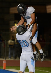 Senior Will Kost lifts running back Wyatt Edmisten into the air after Edmistens touchdown, making the score 21-7 in the second quarter. Photo by Joseph Cline