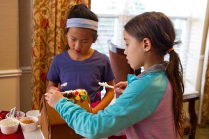 Amelie and Isabelle Wong of Prairie Village set to work decorating their houses at Brighton Gardens Sunday.