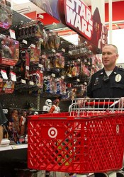 Officer Adam Taylor helps a participant select toys through the Shop with a Cop program.