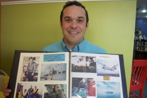 Todd Steinbrecher with a scrapbook of Navy memories and his time on helicopter missions.
