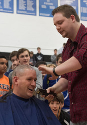 Zach from John's Hairstyling at RanchMart polishes off the shaving job on Coach Shawn Hair's head.