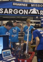 SM East students bring their robot back to the pit after a run.