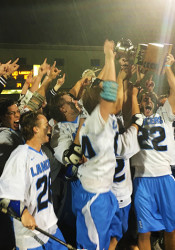 Senior Will Kost hoists the LAKC title cup after the Lancers beat Blue Valley West 18-11 in the finals.