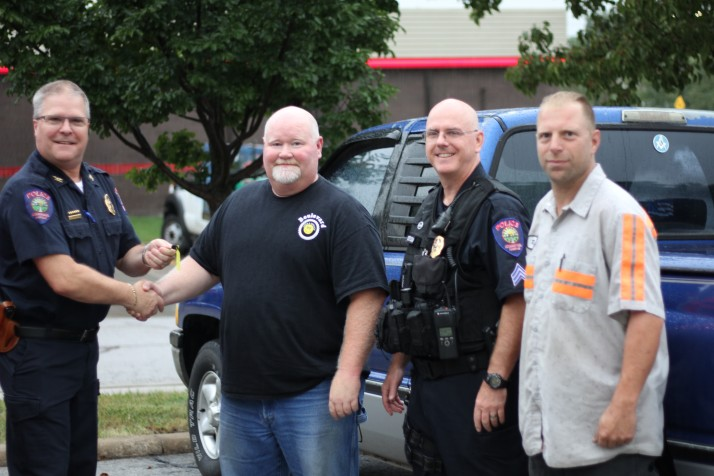 Roeland Park Police Chief John Morris (left) is handed keys to pickup by Blake Breeden of Boulevard Tires. Sgt. Randy Costlow and Richard Moffett of Benfers Tow also were on hand.