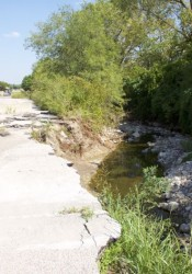 The parking lot along Martway is failing due to erosion in Rock Creek.
