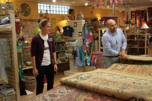 Kendra Frink watches Amir Chaman of the Bunyaad group display hand-made rugs from Pakistan.