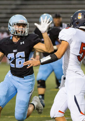 SM East's Cooper Walton pressured Hawks' quarterback Will Scofield in the second quarter.