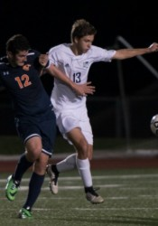 Lancer senior center back Taylor Stover holds off a Olathe East's Adrian Blanco Tuesday evening. The Lancers lost the game 1-0 on header off a free kick.