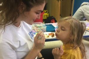 Lauren Cole helps feed a child at Avenue of Life in KCK for her SME Senior Service Day project.