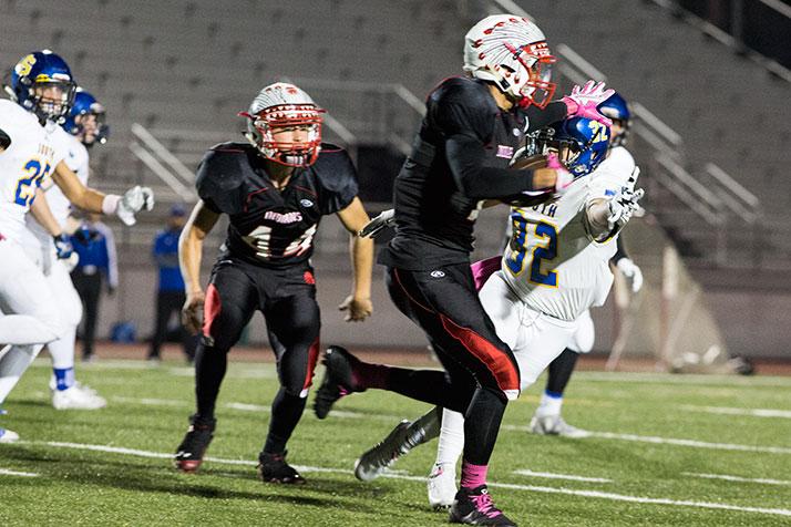 Avante Williams stiffarms a Falcons defender during an early kickoff return.