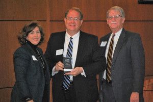 Brad Stratton, center, with UCS Executive Director Julie Brewer and Board Member Tom Robinett.