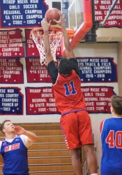 Bishop Miege sophomore Josh Early goes up for a dunk in practice on Monday. Early will start today against St. Thomas Aquinas with the absence of senior Francesco Badocchi.